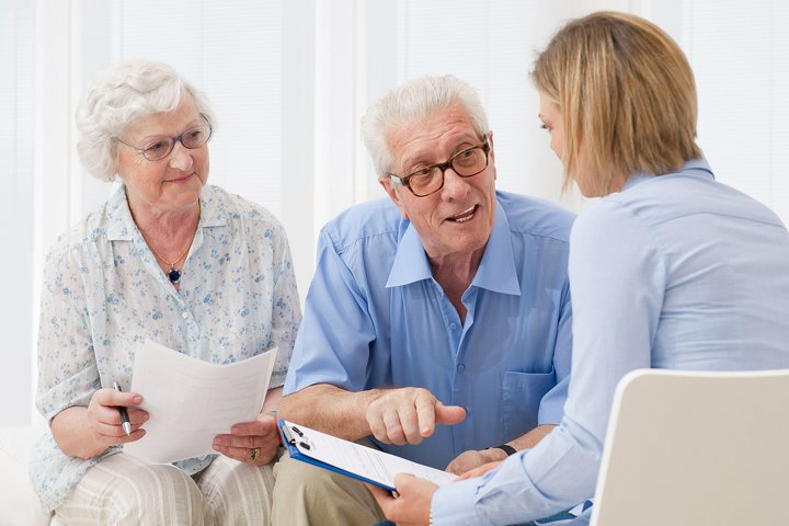 Elderly couple with advisor discussing ageing assistance.